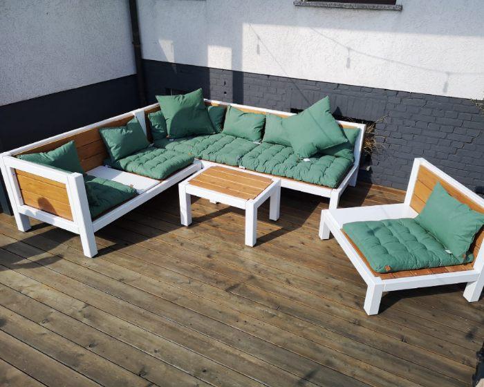 Lounge aus Holz und gruenen Kissen auf der Terrasse