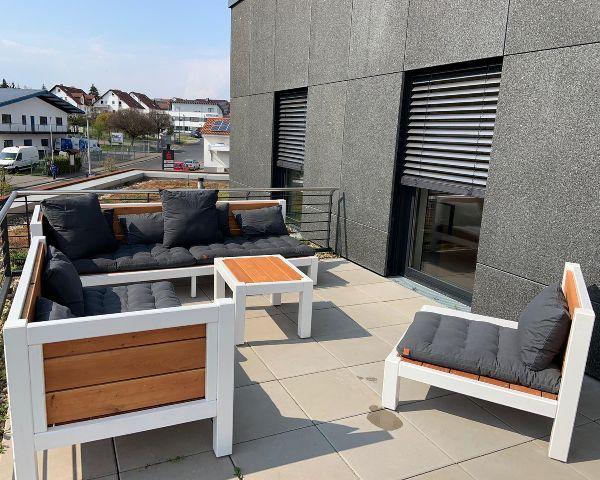 Lounge Set mit schwarzen Kissen auf dem Balkon