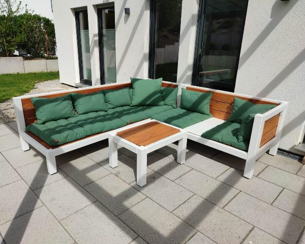 Holzlounge mit gruenen Kissen auf Terrasse